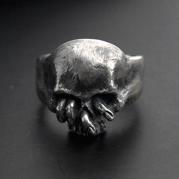Silver skull ring with fingers in the eyes